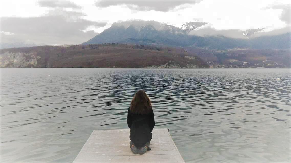 femme assise au bord de l'eau
